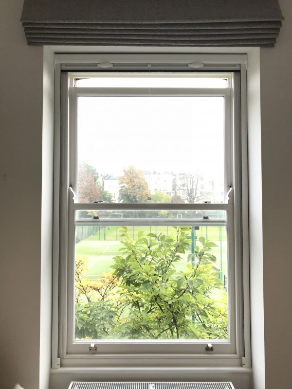 Roller fly screen on sash window